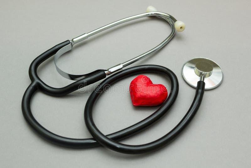 Медицинский стетоскоп и красное сердце изолированные на серой предпо стоковое изображение
