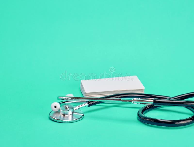 Медицинский стетоскоп и пустые бумажные визитные карточки стоковые фото