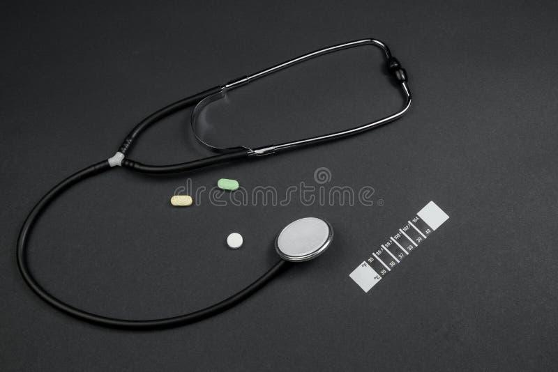 Медицинский стетоскоп, лекарства и термометр-полоска на черном фоне стоковая фотография