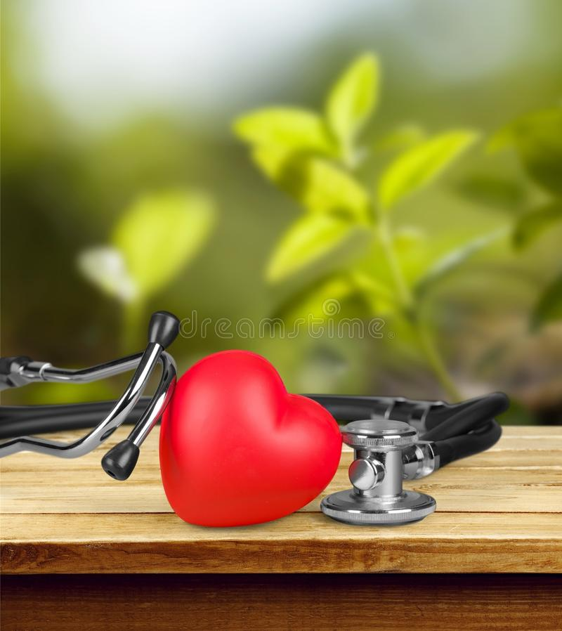 Медицинский стетоскоп при сердце изолированное на деревянном стоковые фото