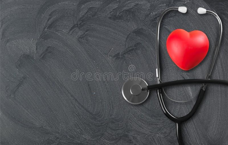 Медицинский стетоскоп с пластичным сердцем на деревянном стоковая фотография rf