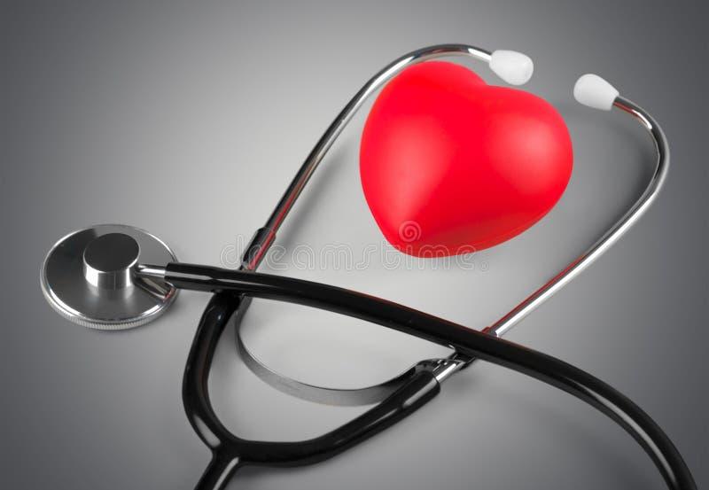Медицинский стетоскоп с пластичным сердцем на деревянном стоковое фото