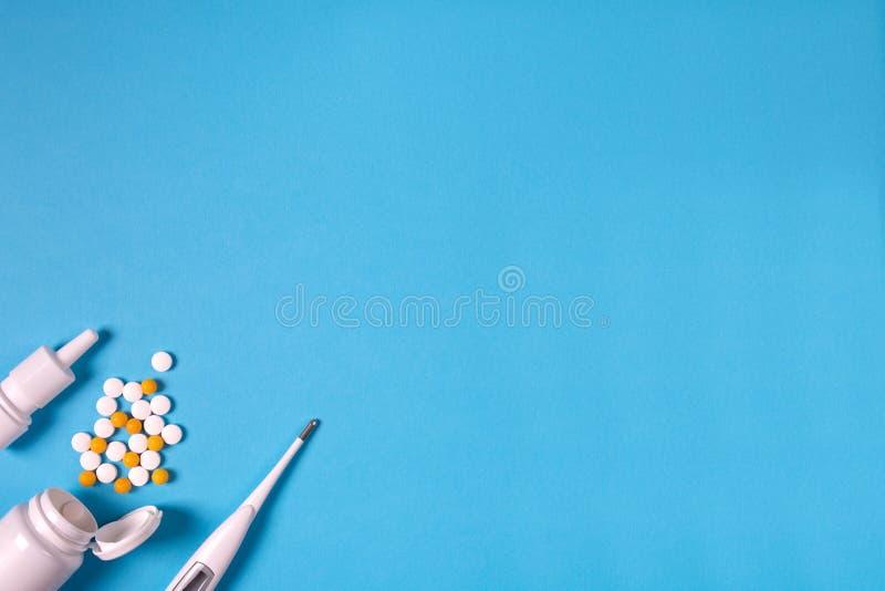 Медицинский электронный термометр, бутылка лекарства с таблетками и брызги для носа на голубой предпосылке стоковая фотография