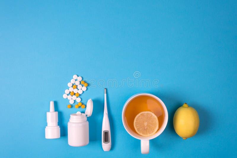 Медицинский электронный термометр, бутылка лекарства с таблетками, брызги для носа и чай с лимоном на голубой предпосылке стоковые фотографии rf