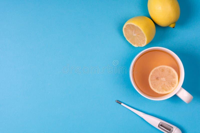 Медицинский электронный термометр, бутылка лекарства с таблетками, брызги для носа и чай с лимоном на голубой предпосылке Здравоо стоковая фотография rf
