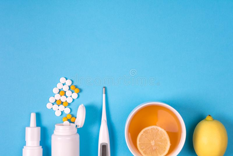 Медицинский электронный термометр, бутылка лекарства с таблетками, брызги для носа и чай с лимоном на голубой предпосылке Здравоо стоковое изображение
