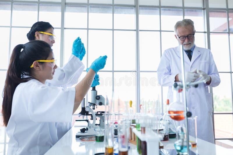 Медицинское исследование и ученые работают с микроскопом и планшетом и пробирками, микропипеткой и результатами анализа в a стоковое фото