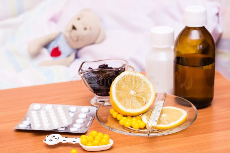 Медицины, витамины, лимон и варенье на таблице на фоне кровати детей стоковые фото