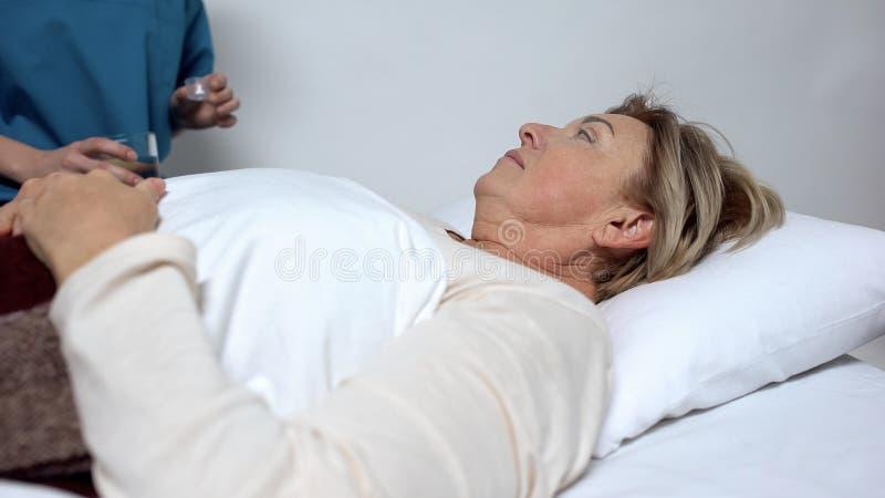 Медсестра давая дозу антибиотиков женскому пациенту после деятельности, больнице стоковые изображения rf