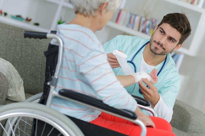 Медсестра делая повязки на пожилой женщине на кресло-коляске стоковые изображения rf