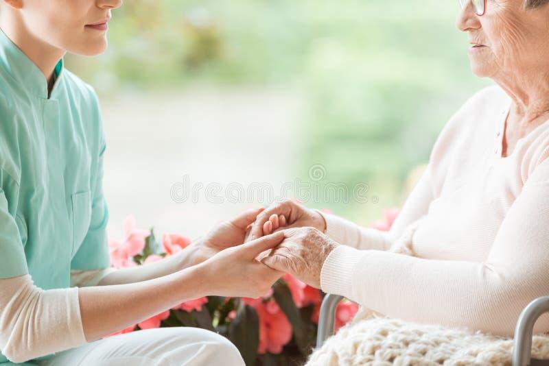 Медсестра держа руки неработающей пожилой женщины стоковое фото rf