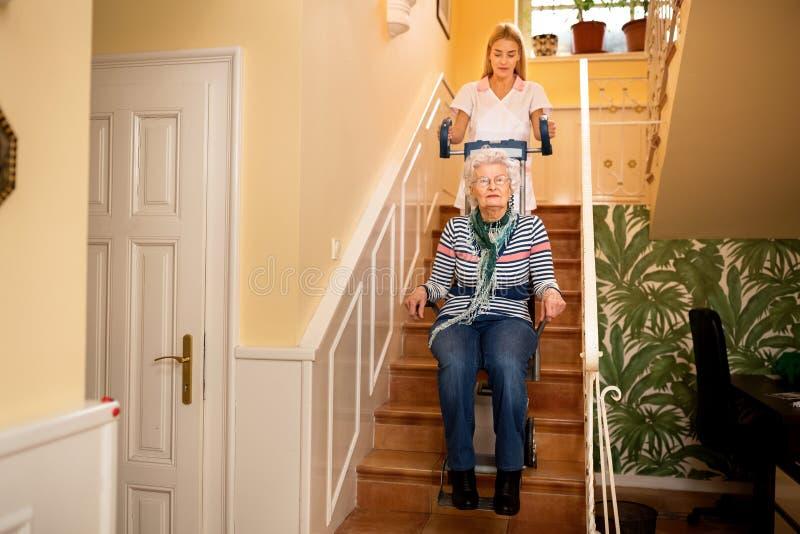 Медсестра помогает старшей женщине взобраться к лестницам стоковые изображения