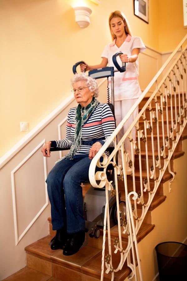 Медсестра помогает старшей женщине взобраться к лестницам стоковое фото