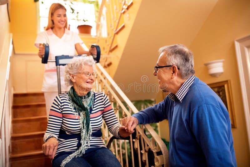 Медсестра помогает старшей женщине взобраться к лестницам стоковое фото rf