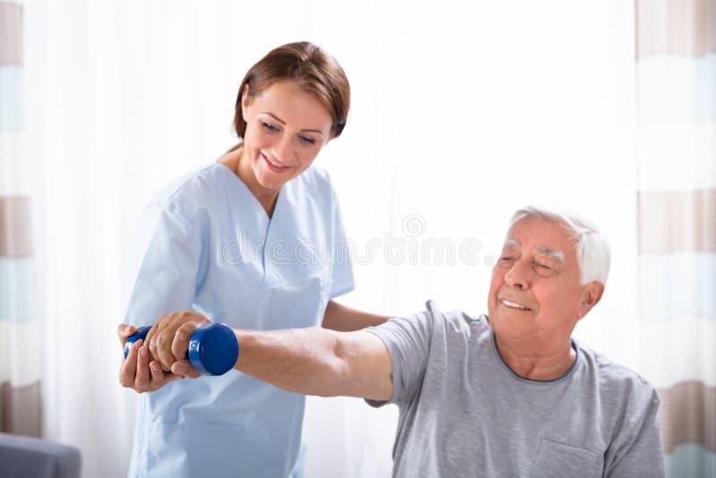 Медсестра помогая старшему человеку с тренировкой гантели стоковое изображение rf