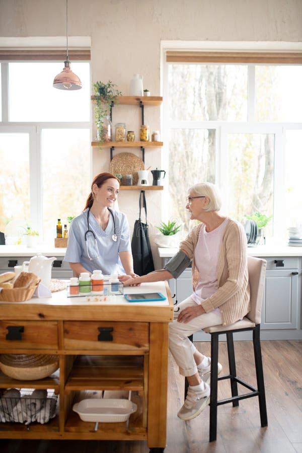 Медсестра посещает старую даму, измеряя давление и говоря стоковое фото rf