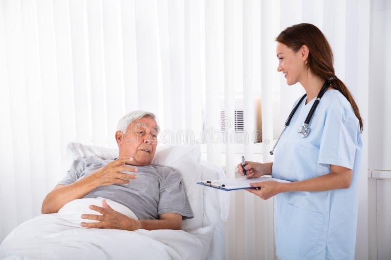 Медсестра с доской сзажимом для бумаги навещая старший пациент стоковая фотография