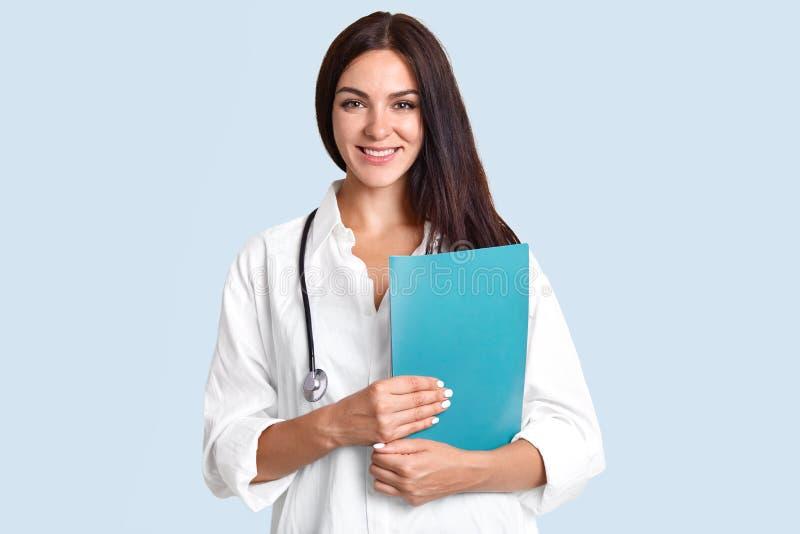Медсестра Posititve женская с стетоскопом делает диагноз, имеет приятное разговаривать с пациентом, объясняет какая медицина, кот стоковые изображения rf