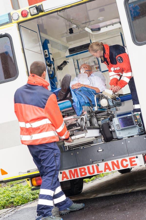 Медсотрудники кладя пациента в помощь автомобиля машины скорой помощи стоковое изображение
