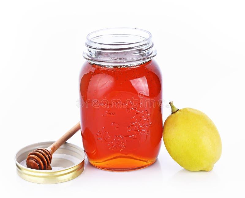 Мед бутылки, лимон на белой предпосылке стоковое изображение