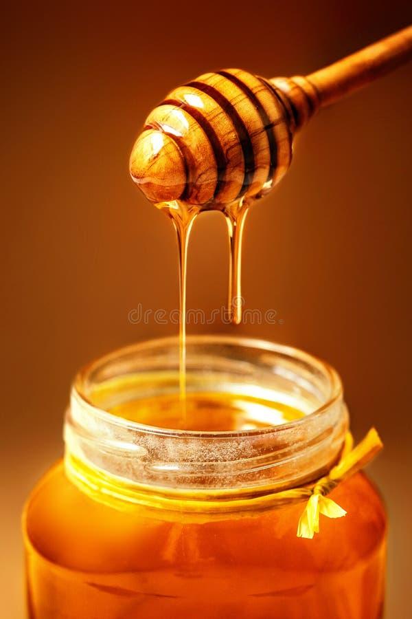 Мед в опарнике с ковшом меда на деревенской предпосылке деревянного стола стоковая фотография