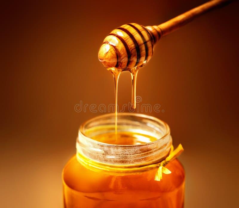 Мед в опарнике с ковшом меда на деревенской предпосылке деревянного стола стоковое фото