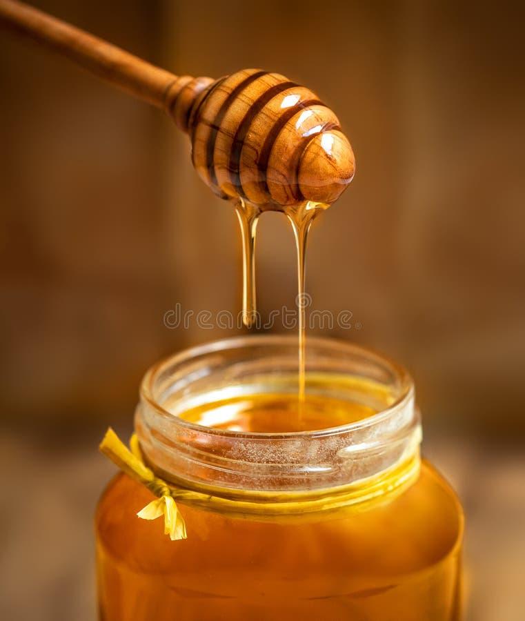 Мед в стеклянном опарнике с ковшом меда на деревенском ба деревянного стола стоковая фотография rf
