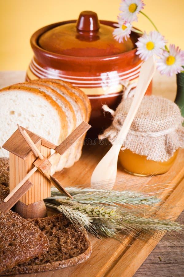 Мед, цветки и хлеб на таблице стоковое фото rf
