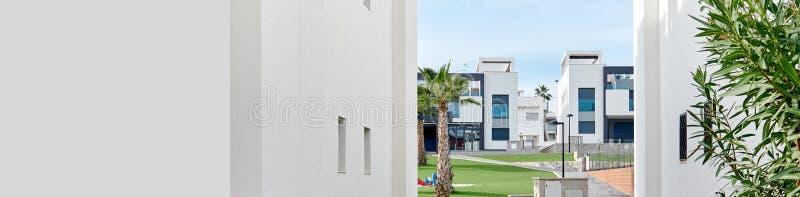 Между взглядом 2 Белых Домов для того чтобы позеленеть лужайку жилой урбанизации, таунхаусы современной архитектуры подобные в ст стоковые фотографии rf