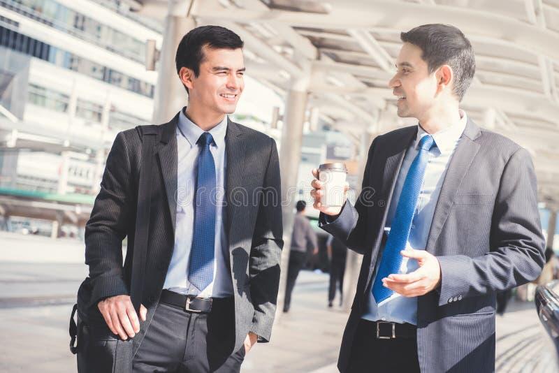 Межрасовые бизнесмены как коллега, идя и говоря в стоковая фотография