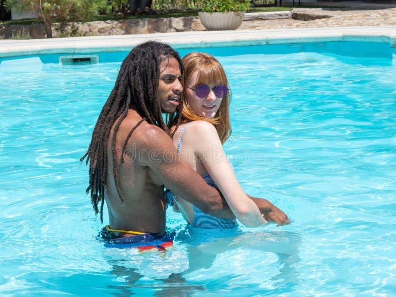 Межрасовые пары в любов, игре в бассейне Девушка очень белые и красные волосы и чернота мальчика стоковая фотография