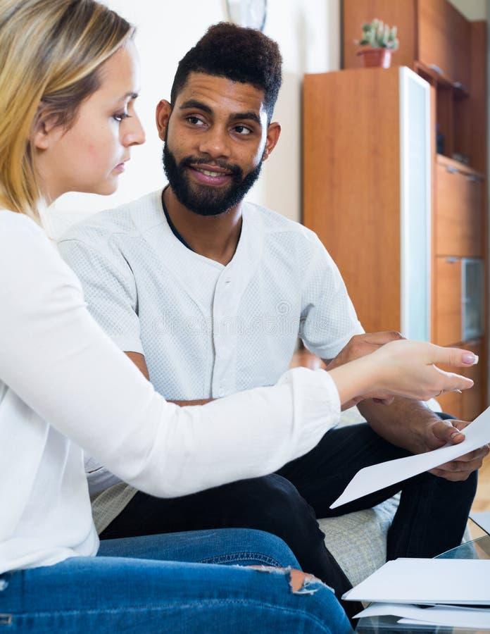 Межрасовые пары обсуждая кренящ предложение для ипотеки дома стоковое изображение