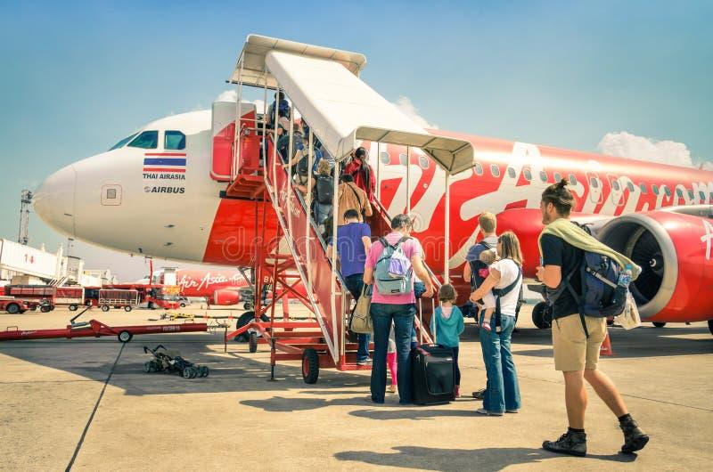 Международные туристские люди всходя на борт полета Air Asia в авиапорт Бангкока стоковая фотография rf