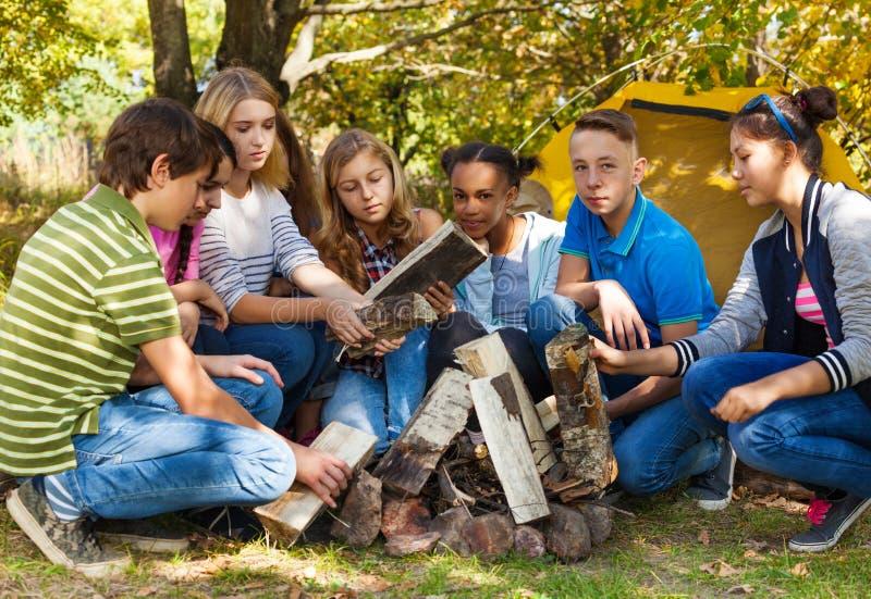 Международный подросток настраивая костер совместно стоковая фотография