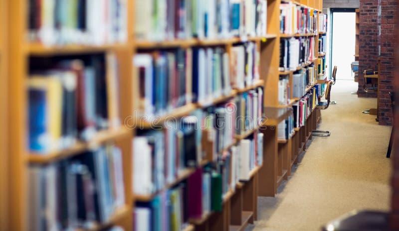 Междурядье вдоль книжных полок в библиотеке колледжа стоковые фото