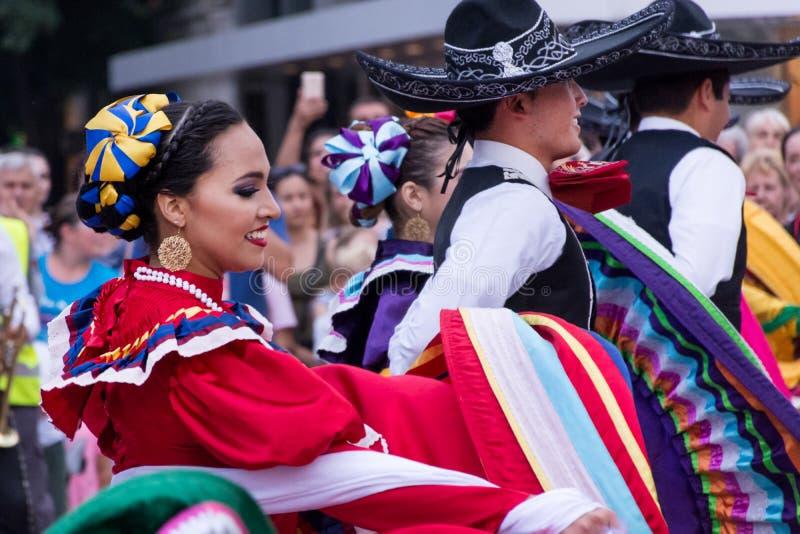 Мексиканец укомплектовывает личным составом и девушки в традиционном красочном костюме людей танцуют стоковые изображения