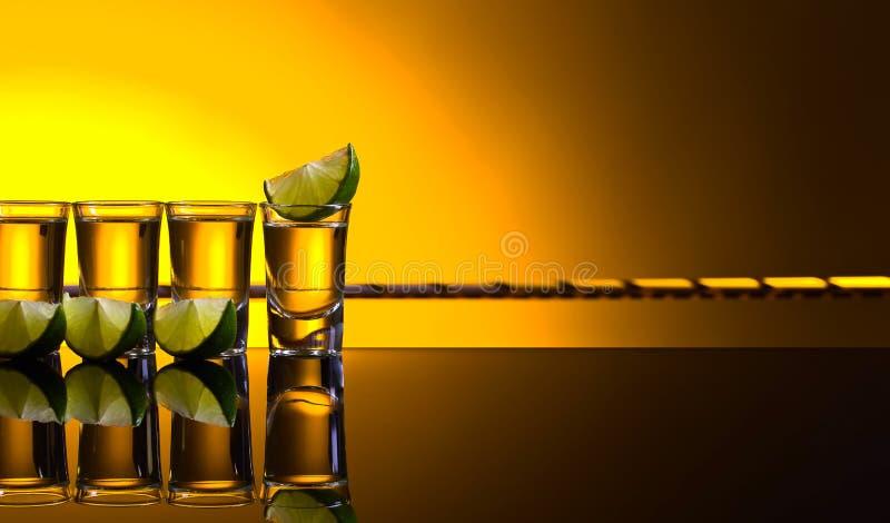 Мексиканские стекла текила золота вкратце с известкой стоковые фото