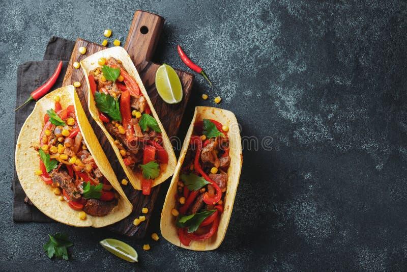 Мексиканские тако с говядиной, овощами и сальсой Пастор al тако на деревянной доске на черной предпосылке Взгляд сверху с космосо стоковые фотографии rf