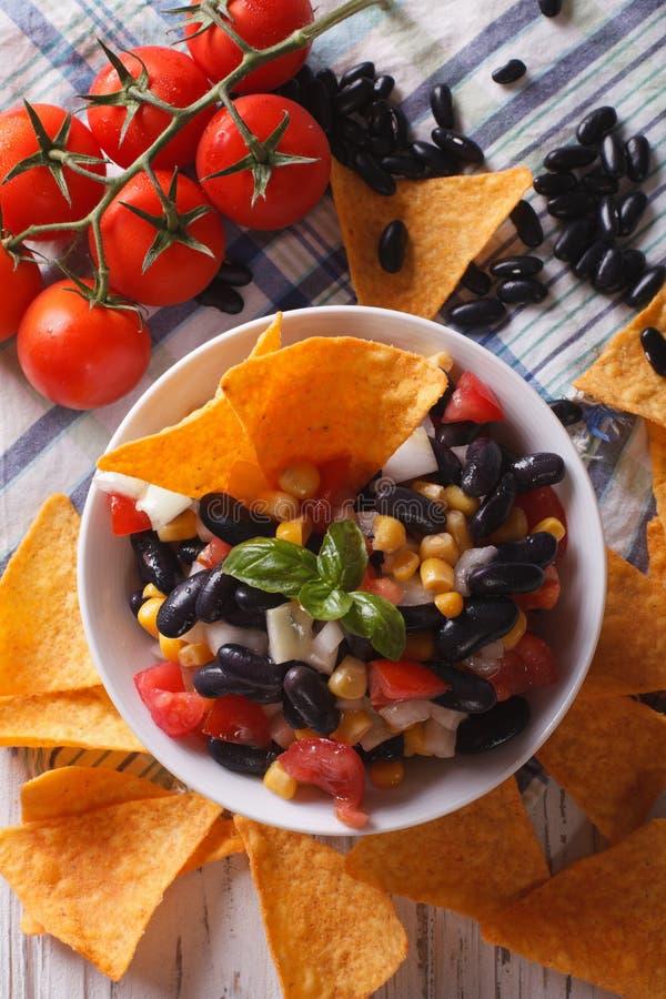 Мексиканский конец-вверх nachos обломоков сальсы и мозоли Вертикальное взгляд сверху стоковое изображение rf