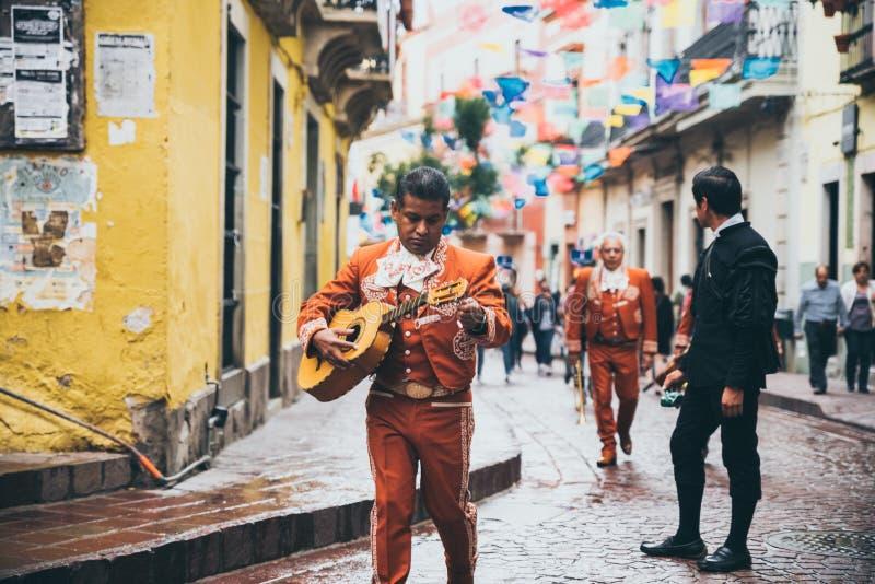 МЕКСИКА - 23-ЬЕ СЕНТЯБРЯ: Гитарист Mariachi идя в цвет стоковое фото