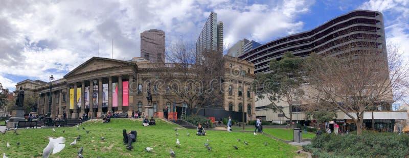 МЕЛЬБУРН, АВСТРАЛИЯ - 6-ОЕ СЕНТЯБРЯ 2018: Панорамный вид государственной библиотеки и людей Виктория в парке Мельбурн привлекает  стоковое изображение