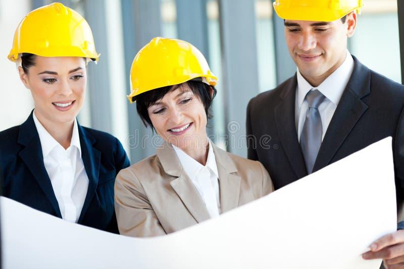 Менеджеры конструкции обсуждая проект стоковые изображения