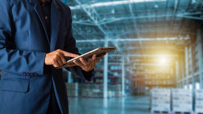 Менеджер бизнесмена используя проверку и управление таблетки для работников с современными торговыми снабжениями склада индустрия стоковые фото