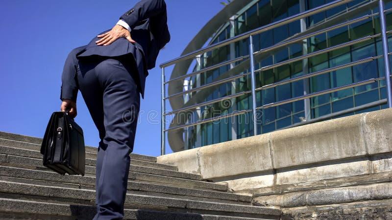 Менеджер в костюме страдая от более низкой боли в спине, сместил диск, симптом заболеванием стоковые изображения rf