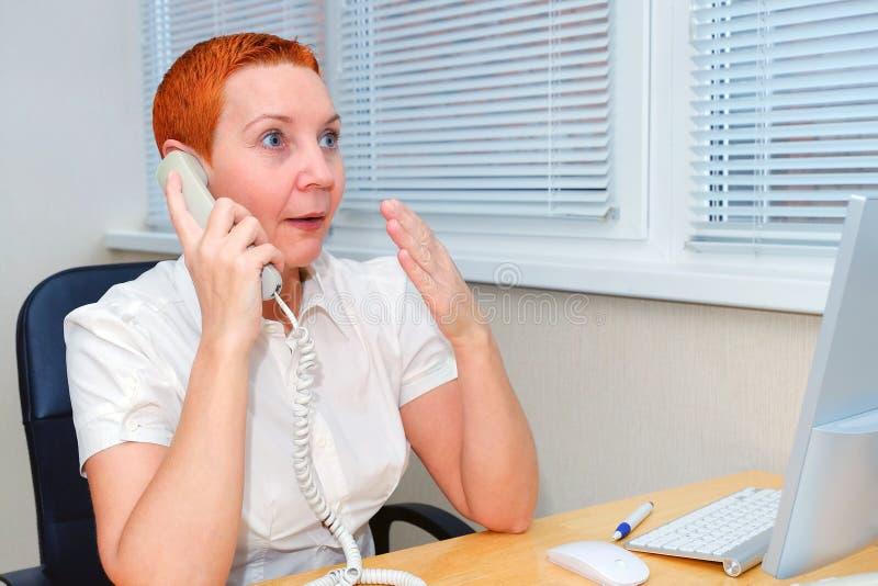 Менеджер офиса говоря на телефоне Выражения лица, эмоция радостного сюрприза стоковое фото