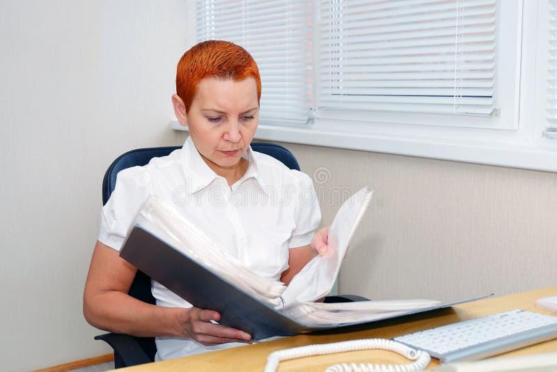 Менеджер офиса девушки смотря документы сконцентрировано стоковая фотография rf