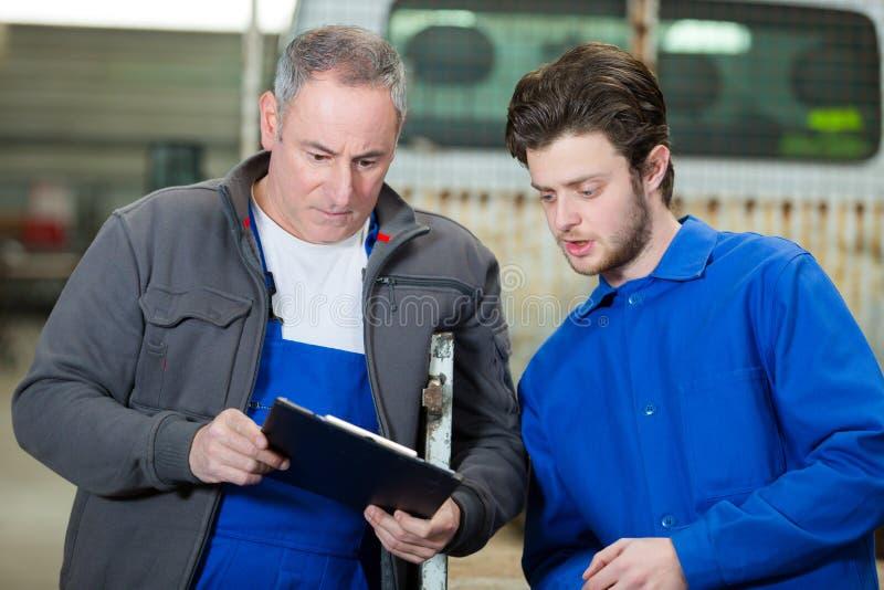 Менеджер фабрики и инженер подмастерья смотря доску сзажимом для бумаги стоковое изображение rf