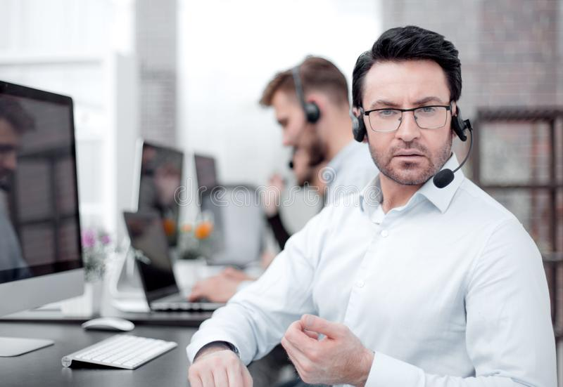 Менеджер центра телефонного обслуживания сидя на его столе стоковые фото