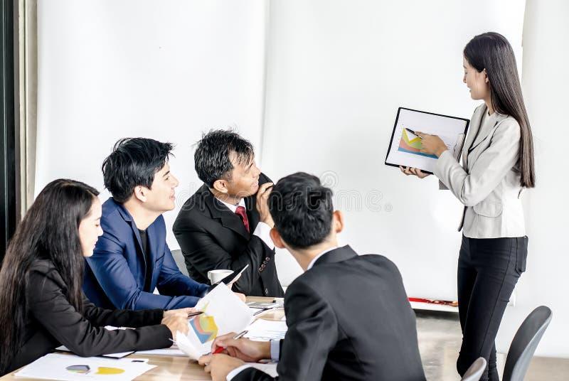 Менеджер Oung стоя делающ представлением финансовую диаграмму пока другие слушая к ей стоковое фото