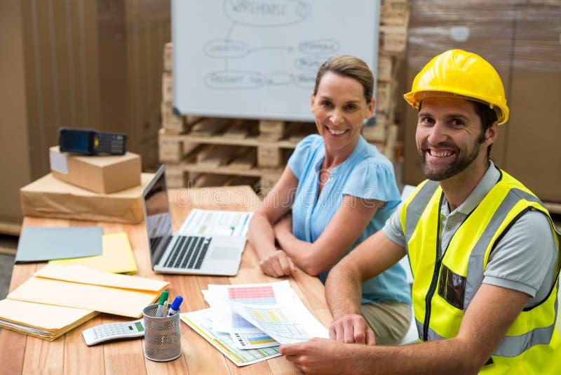 Менеджеры и работники склада усмехаясь в складе стоковое фото rf
